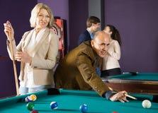 Elderly couple plays billiards. Ordinario mature couple plays billiards royalty free stock image