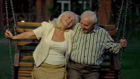 Elderly couple on porch swing. Man and woman smiling, evening. Two happy souls stock video