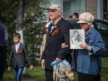 An elderly couple with a portrait of a relative take part in the Immortal regiment on 9 May, 2016 in Ulyanovsk, Russia Stock Photos