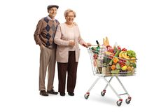 Elderly couple posing with a shopping cart. Full length portrait of an elderly couple posing with a shopping cart isolated on white background royalty free stock images