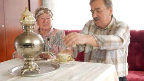 An elderly couple prepares tea with a vintage Russian kettle samovar. A man with a mustache pours tea for his wife stock video