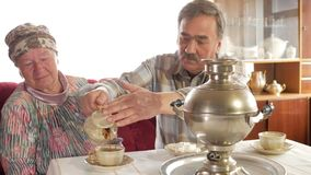 An elderly couple prepares tea with a vintage Russian kettle samovar. A man with a mustache pours tea for his wife stock video footage