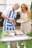 Elderly couple preparing barbecue Royalty Free Stock Photo