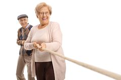 Elderly couple pulling a rope. Isolated on white background royalty free stock images