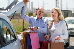 Elderly couple putting bags  in trunk Stock Photography