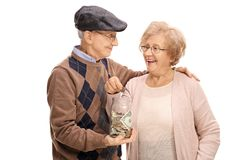 Elderly couple putting a coin into a money jar. Isolated on white background royalty free stock image