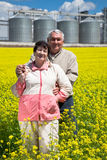 Elderly couple on rapeseed field Stock Photography