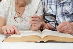 An elderly couple reading a book Stock Photography