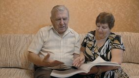 Elderly couple reading a book, on the couch, they are happy together. 4K stock footage