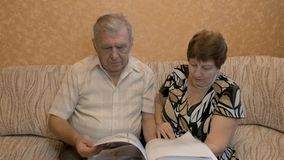 Elderly couple reading a book, on the couch, they are happy together. 4K stock video
