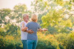 Elderly couple relaxing in garden at sunset. Concept couple elder love stock photos