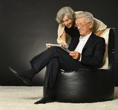 Elderly couple reading newspaper Stock Photos