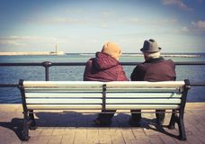Elderly couple sitting on a bench stock images