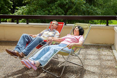 The elderly couple relax in lounges on sunny terrace Stock Photos