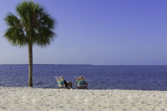 Elderly Couple Relaxing on the beach. Sitting in chairs under a palm tree reading Royalty Free Stock Photos