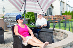 Elderly couple relaxing on an upmarket patio Royalty Free Stock Images