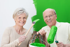 Elderly couple renovating their house. Painting the wall a vivid shade of green as they hold up the can of paint and their roller and brush stock images