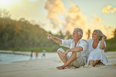 Elderly couple rest at tropical beach. Happy elderly couple rest at tropical beach Royalty Free Stock Image