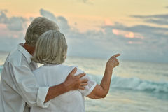 Elderly couple rest at tropical beach. Happy elderly couple rest at tropical beach Stock Photo
