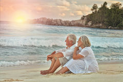 Elderly couple rest at tropical beach. Happy elderly couple rest at tropical beach Royalty Free Stock Photo