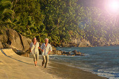 Elderly couple rest at tropical beach. Happy elderly couple rest at tropical beach Royalty Free Stock Photography