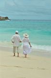 Elderly couple rest at tropical beach. Happy elderly couple rest at tropical beach,back view Royalty Free Stock Photography