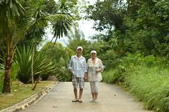 Elderly couple rest at tropical beach. Happy elderly couple resting at tropical beach Royalty Free Stock Photo
