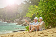 Elderly couple rest at tropical beach Stock Photography