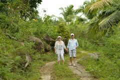 Elderly couple rest at tropical beach. Happy elderly couple resting at tropical beach Royalty Free Stock Image