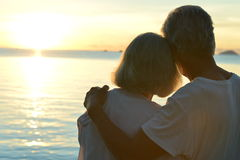 Elderly couple rest at tropical beach. Happy elderly couple rest at tropical beach at sunset Royalty Free Stock Photo