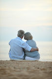 Elderly couple rest at tropical beach. Happy elderly couple rest at tropical beach at sunset,back view Stock Photo