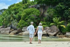 Elderly couple rest at tropical resort. Happy elderly couple on sandy beach near tropical resort Stock Photography