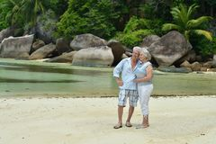 Elderly couple rest at tropical resort. Happy elderly couple on sandy beach near tropical resort Royalty Free Stock Photography