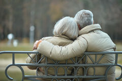 Elderly couple resting at autumn park. Elderly couple resting together on bench at autumn park ,back view royalty free stock photos
