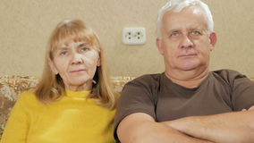 Elderly couple resting at home on the couch and looking at the camera. Elderly couple resting at home on the couch and looking at the camera stock video footage