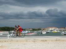 An elderly couple riding a bike on the waterfront of Medulin. Croatia, Istra, Medulin - July 18, 2010 stock images