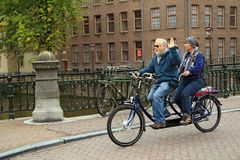 An elderly couple riding the tandem bike. Amsterdam, Netherlands. An elderly couple riding the tandem bike in the historical center. The intersection of the Royalty Free Stock Images