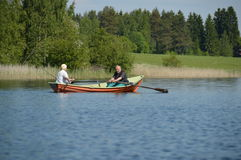 Senior hobbies: elderly couple rowing in a boat with fishing rods - Joensuu, Finland - June 2015. Elderly man and woman photographed in Finland, Northern Europe royalty free stock photo