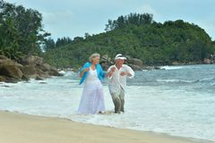 Elderly couple running  on beach Royalty Free Stock Images