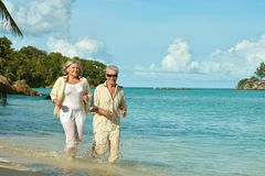 Elderly couple running  on beach Stock Photo