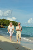 Elderly couple running  on beach Royalty Free Stock Photography