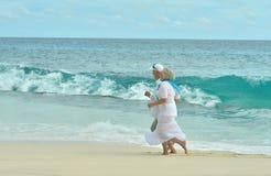 Elderly couple running  on beach Stock Photos