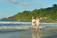Elderly couple running  on beach Royalty Free Stock Image