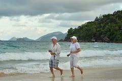 Elderly couple running  on beach Stock Photography