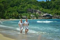 Elderly couple running  on beach Stock Photo