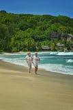 Elderly couple running  on beach Stock Image
