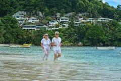 Elderly couple running  on beach Royalty Free Stock Photo