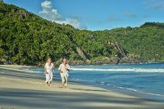 Elderly couple running  on beach Stock Images