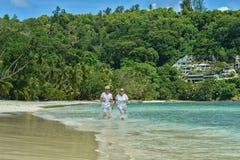Elderly couple running  on beach Royalty Free Stock Photography