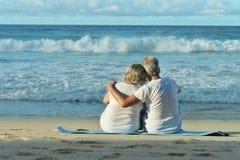 Elderly couple running on beach. Happy elderly couple resting on sandy beach near tropical resort Royalty Free Stock Photo